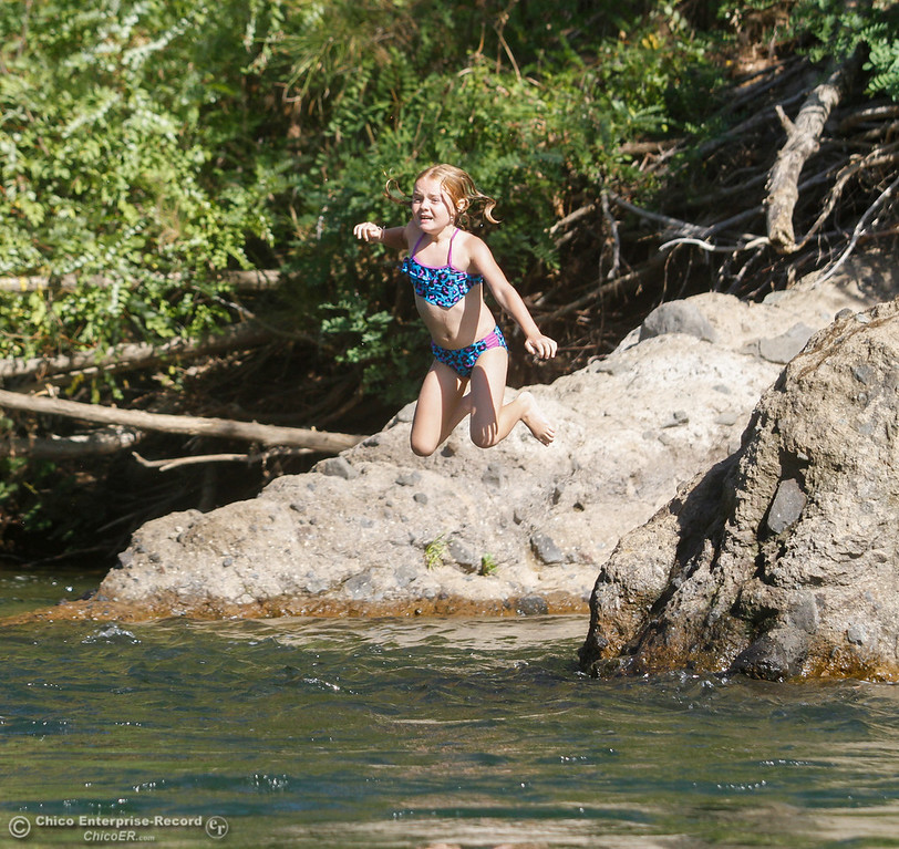 . Sadie Patterson jumps into a swimming hole along Butte Creek under the Honey Run Covered Bridge Tuesday July 25, 2017 in Chico, California. (Emily Bertolino -- Enterprise-Record)