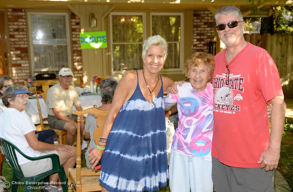 . Birthday girl Dorothy Sweeney, AKA Mayor of Bidwell Avenue, center, gets hugs from daughter Luanne Park, left and neighbor Paul Olson as she offers donuts to friends and neighbors in celebration of her 92nd birthday Friday July 28, 2017. (Bill Husa -- Enterprise-Record)
