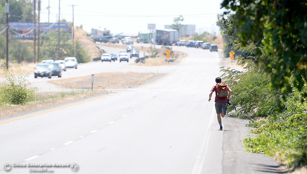 . Reporter Eli Stillman runs toward the scene of an accident on a very hot day Thursday.  Eastbound Skyway was completely closed for a time following a two vehicle rollover collision below Spanish Garden Drive involving a Ford Focus and a Ford Fusion Thursday July 27, 2017. (Bill Husa -- Enterprise-Record)
