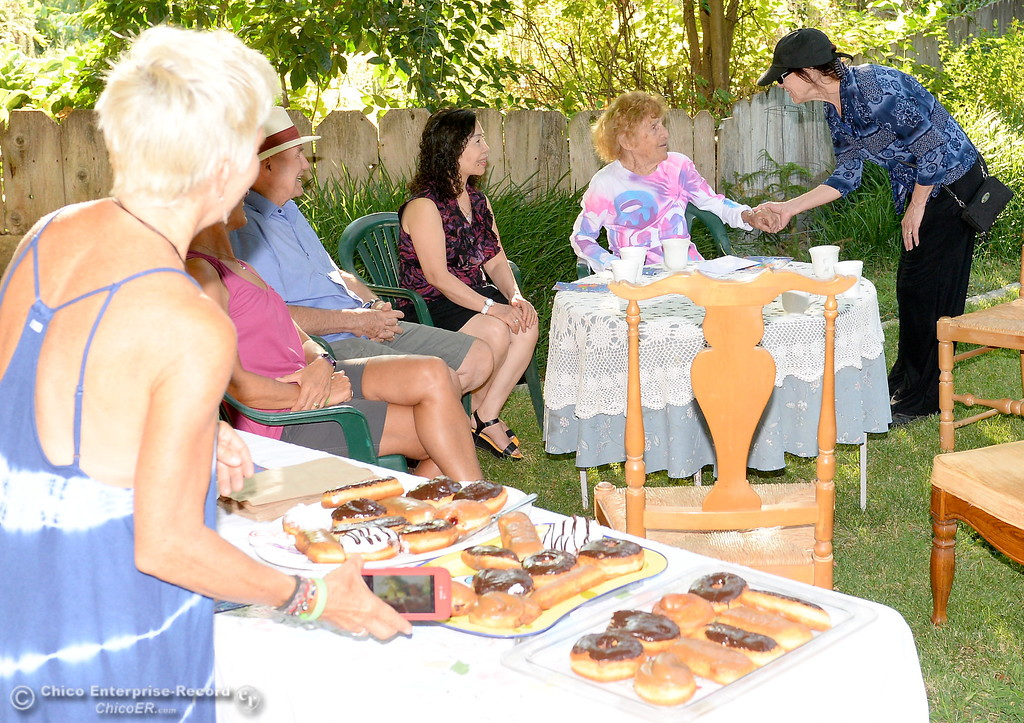 . Friends and neighbors gather around a table to celebrate the 92nd birthday of Dorothy Sweeney, AKA Mayor of Bidwell Avenue as she offers donuts to friends Friday July 28, 2017. Safeway donated the donuts for the event. (Bill Husa -- Enterprise-Record)