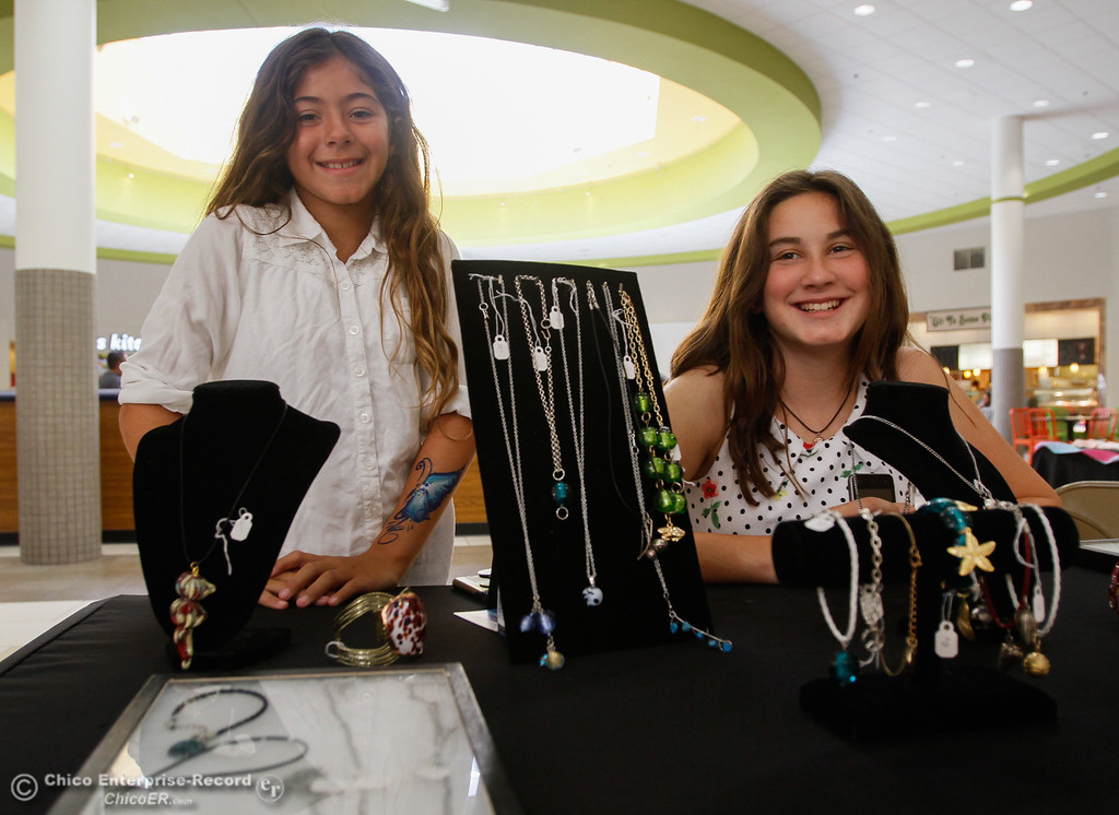 . Phoenix, 10, and Denise 12, of Gridley talk about the jewelry they make from recycled glass work during the Biz Kids showcase Saturday July 29, 2017 at the Chico Mall in Chico, California. (Emily Bertolino -- Enterprise- Record)