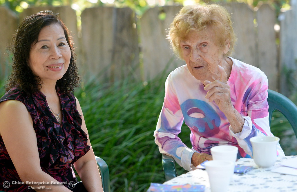 . Birthday girl Dorothy Sweeney, AKA Mayor of Bidwell Avenue at right, offers a donut to neighbor On Le as she celebrates her 92nd birthday Friday July 28, 2017. (Bill Husa -- Enterprise-Record)
