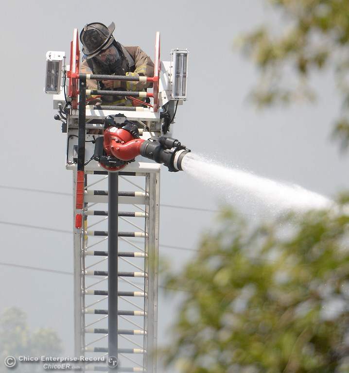 . A firefighter on a ladder truck battles the fire from above during a fire in a mobile home on Aster Drive at Casa De Flores  Mobile Home Park Tuesday Aug. 8, 2017. Ammunition stored in the residence hindered fire suppression and added difficulty in fighting the fire. (Bill Husa -- Enterprise-Record)