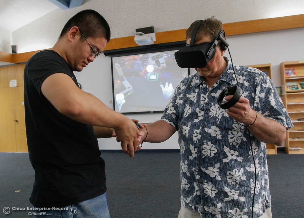 . Librarian assistant Alex Chen helps James Chiarottino put on an Oculus virtual reality headset as library patrons take part in an Oculus virtual reality experience August 8, 2017 at Butte County Library Chico Branch in Chico, California. (Emily Bertolino -- Enterprise- Record)