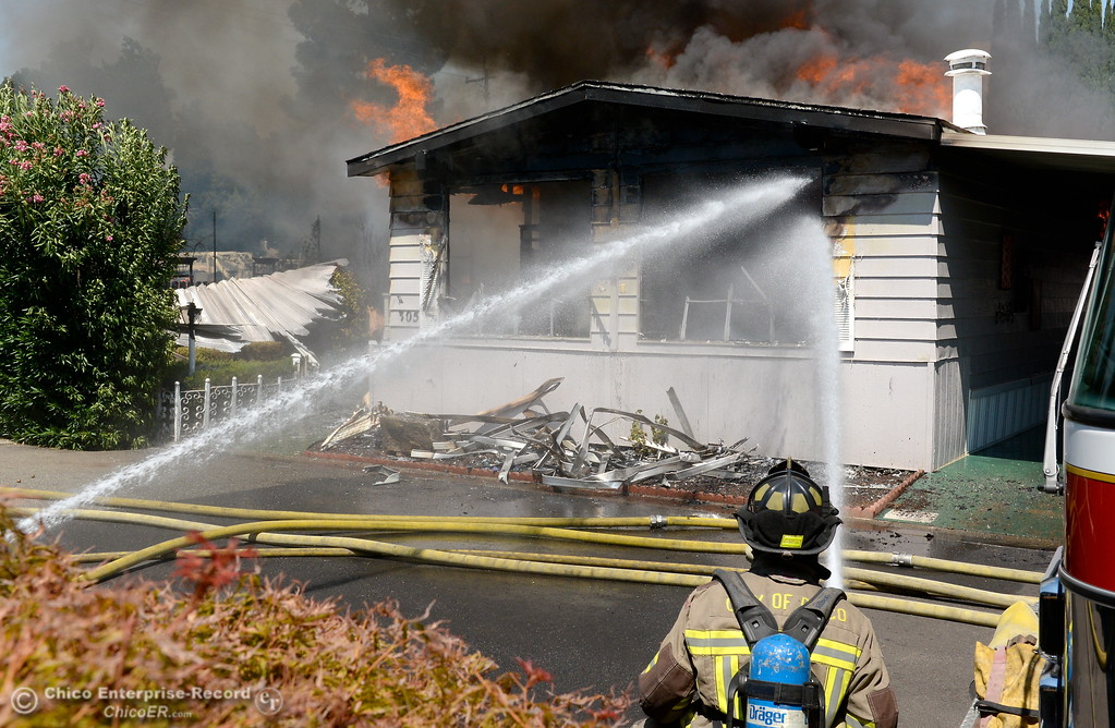 . A firefighter gets water in through a window as Chico Firefighters battle a fire in a mobile home on Aster Drive at Casa De Flores Mobile Home Park Tuesday Aug. 8, 2017. Ammunition stored in the residence added an element of danger and difficulty to fighting the fire. (Bill Husa -- Enterprise-Record)