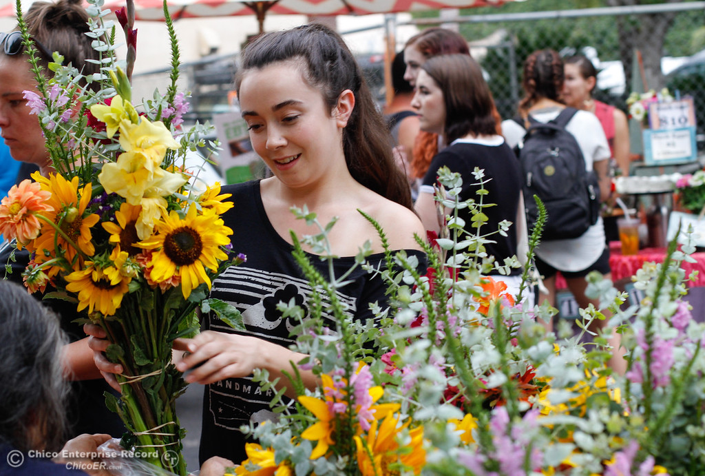 . Amelia Carmosino picks out flowers at the Thursday Night Farmers Market August 10, 2017  in Chico, California. (Emily Bertolino -- Enterprise- Record)