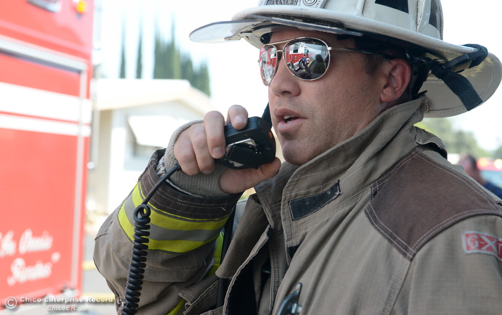. Chico Fire Division Chief Jesse Alexander keeps in contact via radio as firefighters battle a fire in a mobile home on Aster Drive at Casa De Flores  Mobile Home Park Tuesday Aug. 8, 2017. Ammunition stored in the residence hindered fire suppression and added difficulty in fighting the fire. (Bill Husa -- Enterprise-Record)