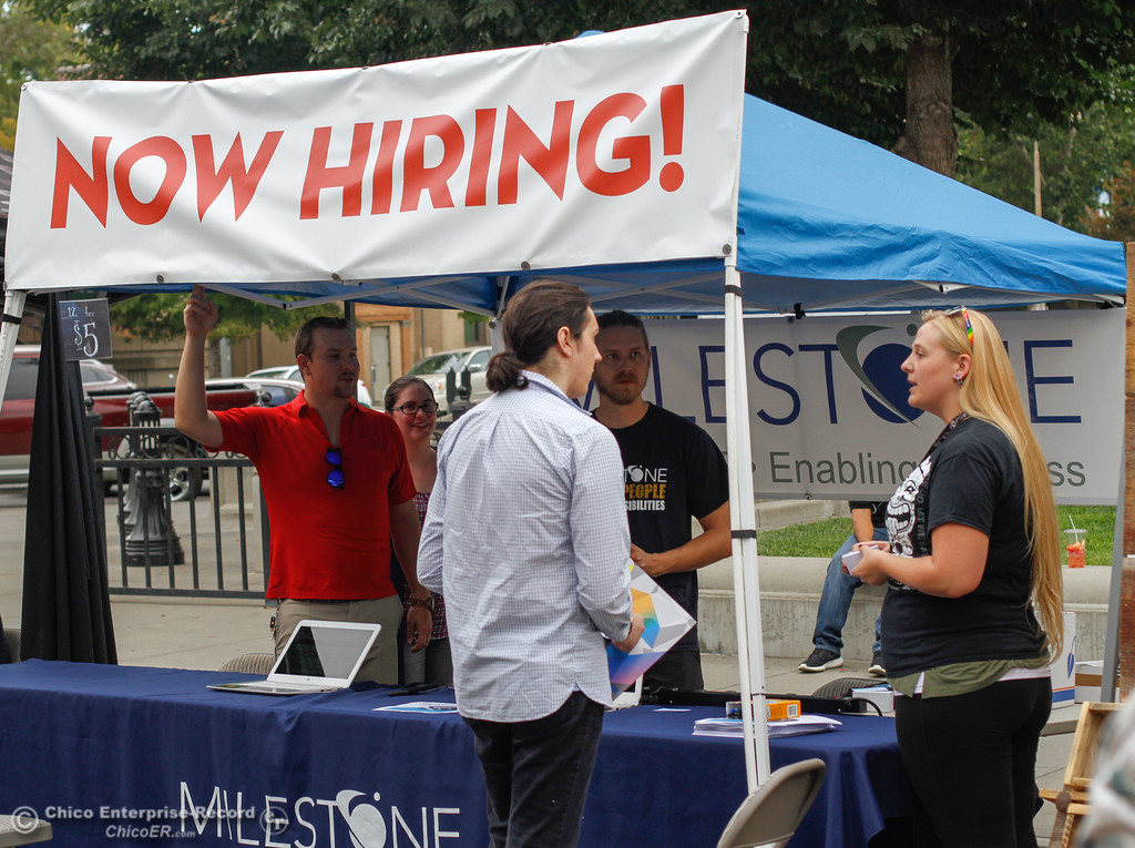 . The staff at Milestone Technologies talk with people who may be looking for jobs with the company August 10, 2017 at the Thursday Night Farmers Market  in Chico, California. (Emily Bertolino -- Enterprise- Record)
