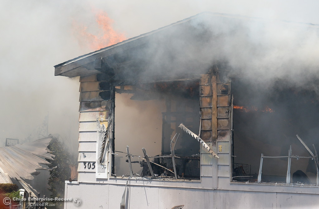 . Firefighters work to contain a fire in a mobile home on Aster Drive at Casa De Flores  Mobile Home Park Tuesday Aug. 8, 2017. Ammunition stored in the residence added difficulty and danger in fighting the fire. (Bill Husa -- Enterprise-Record)