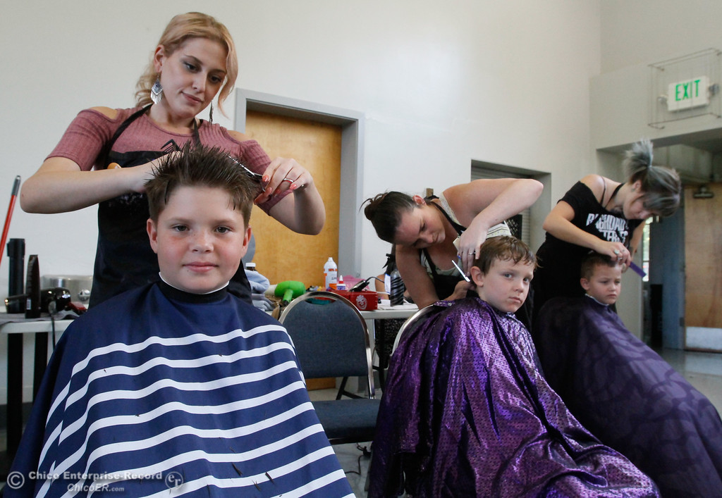 . Jason Blagden (12), Christian Truett (6) and Landyn Watts (6) get hair cuts from Marisa Bhojak, Haley Hutler and Kristy Nall (left to right) during the Back to School Connect event organized by School Ties at the Butte County Office of Education Tuesday August 8, 2017 at Chico Junior High School in Chico, California. (Emily Bertolino -- Enterprise- Record)