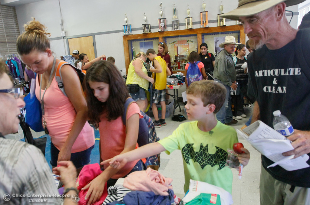 . Tanra Baxter, Kymber Baxter (12), Christian Truett (6), and Tim Truett pick out new clothes during the Back to School Connect even organized by School Ties at the Butte County Office of Education Tuesday August 8, 2017 at Chico Junior High School in Chico, California. (Emily Bertolino -- Enterprise- Record)