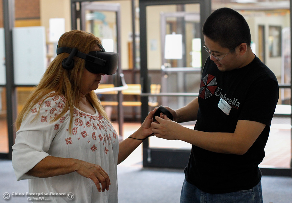 . Librarian assistant Alex Chen helps Alexandra Lejune put on an Oculus virtual reality headset as library patrons take part in an Oculus virtual reality experience August 8, 2017 at Butte County Library Chico Branch in Chico, California. (Emily Bertolino -- Enterprise- Record)