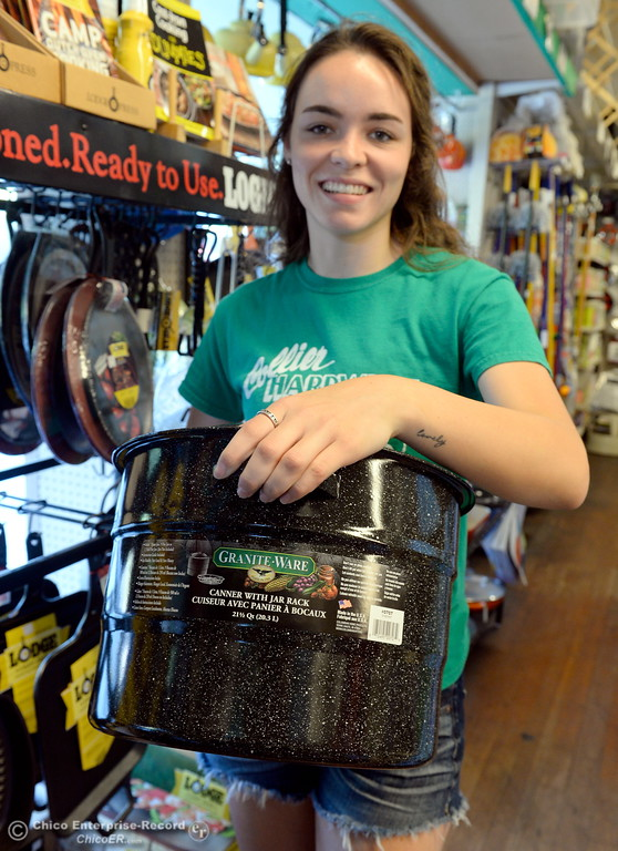 . Employee Johanna Faaborg holds a 21 quart canner with jar rack near the canning supplies available at Collier Hardware in Chico, Calif. Tues. Aug. 8, 2017. (Bill Husa -- Enterprise-Record)