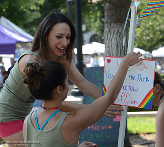 Angela Gonzales, top and Julia Moreno hang a sign offereing free yoga Sunday morning during Stonewall Alliance's Chico Pride 2016 event Saturday, Aug. 20, 2016, at City Plaza in Chico, California. (Dan Reidel -- Enterprise-Record)