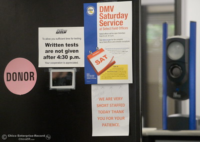 A sign is posted telling customers they are very short staffed and have a DMV Saturday service are seen as people wait in line at the DMV in Chico, Calif. Thursday July 26, 2018. (Bill Husa -- Enterprise-Record)