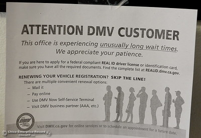 Signs about wait times are seen posted at various places throughout the DMV as people wait in line at the DMV in Chico, Calif. Thursday July 26, 2018. (Bill Husa -- Enterprise-Record)