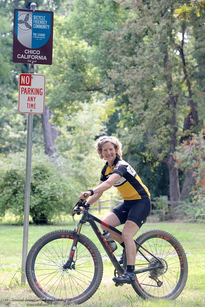 "Janine Rood smiles as she rides by the ""Bike Friendly City"" sign in Bidwell Park Friday Aug. 4, 2016. Rood is retiring from her position as Executive Director of Chico Velo. (Bill Husa -- Enterprise-Record)"