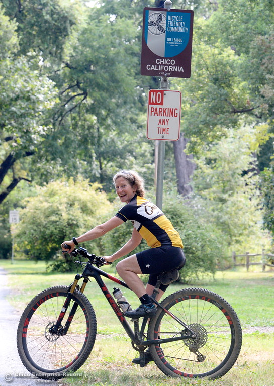 ". Janine Rood smiles as she rides by the ""Bike Friendly City\"" sign in Bidwell Park Friday Aug. 4, 2016. Rood is retiring from her position as Executive Director of Chico Velo. (Bill Husa -- Enterprise-Record)"