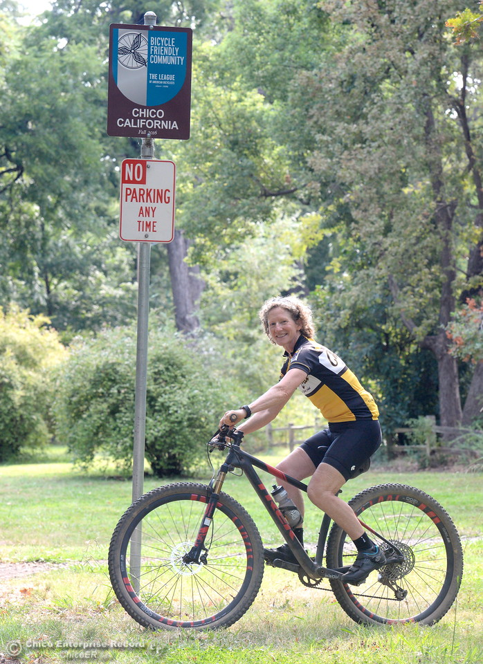 """Janine Rood smiles as she rides by the """"Bike Friendly City"""" sign in Bidwell Park Friday Aug. 4, 2016. Rood is retiring from her position as Executive Director of Chico Velo. (Bill Husa -- Enterprise-Record)"""