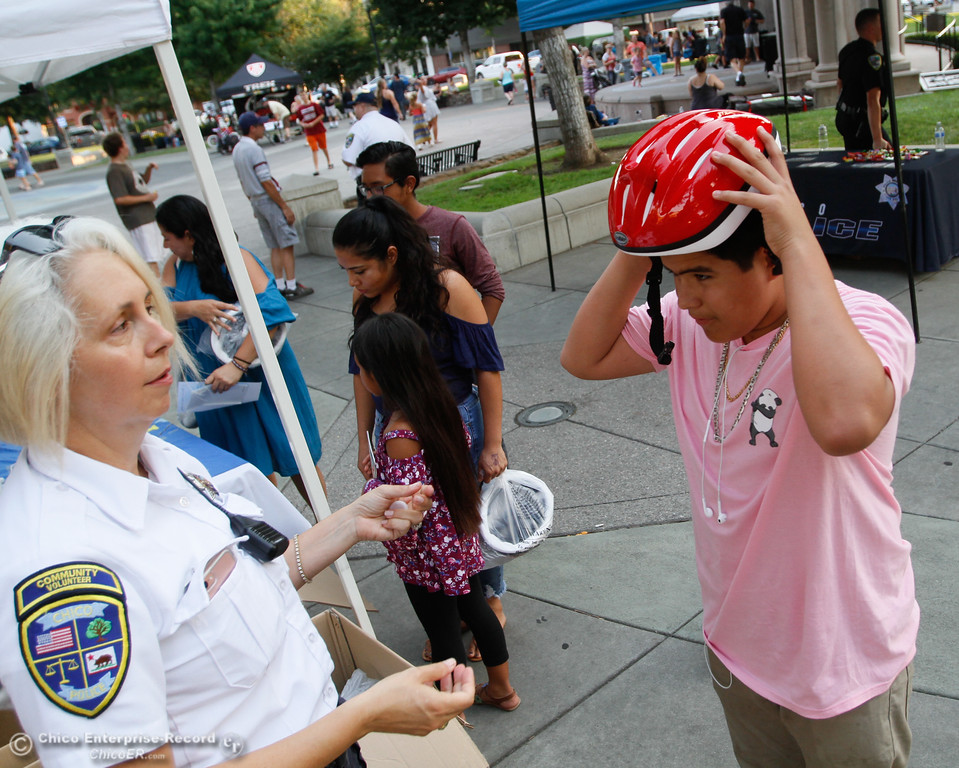 . Chico VIPS officer Kristi Bennett (left) helps Manuel Garcia fit his new helmet during the annual National Night Out Tuesday August 1, 2017 in Chico, California. (Emily Bertolino -- Enterprise- Record)
