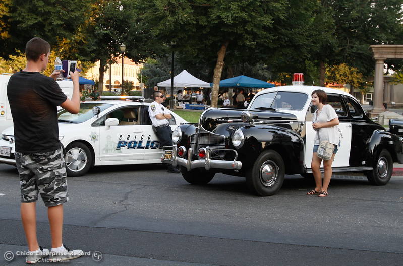 Isaiah Lacombe takes a picture of Amanda Meyers in front of the Chico VIPS historic 1940 police car during the annual National Night Out Tuesday August 1, 2017 in Chico, California. (Emily Bertolino -- Enterprise- Record)