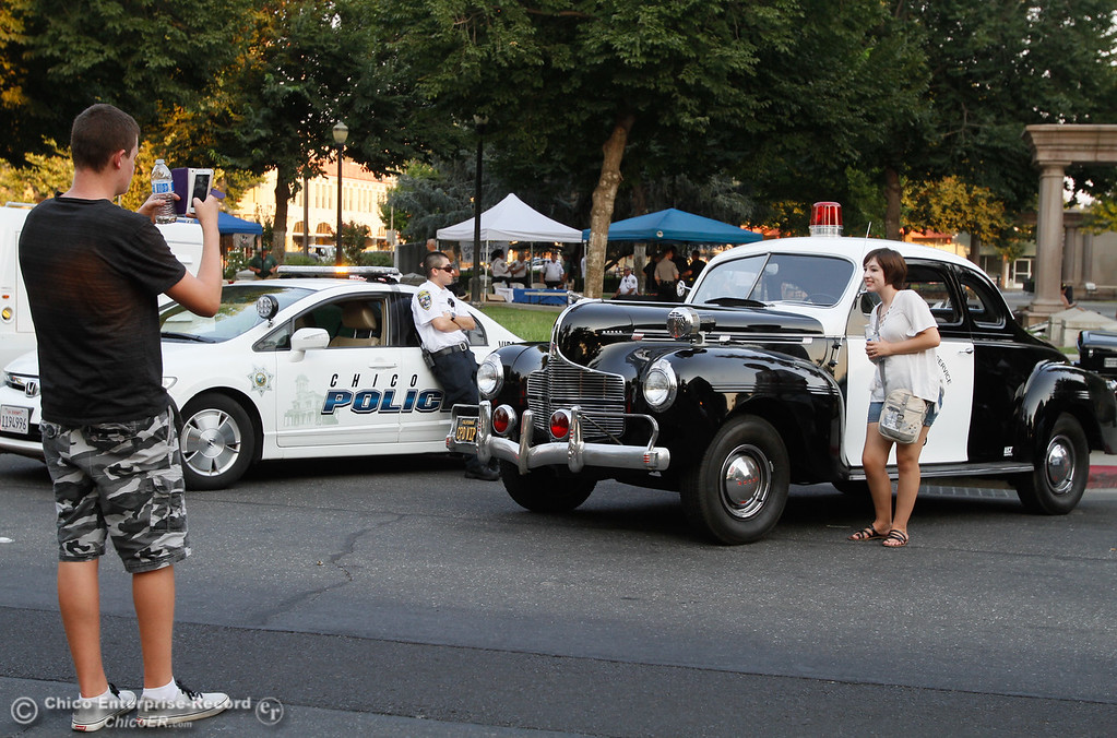 . Isaiah Lacombe takes a picture of Amanda Meyers in front of the Chico VIPS historic 1940 police car during the annual National Night Out Tuesday August 1, 2017 in Chico, California. (Emily Bertolino -- Enterprise- Record)