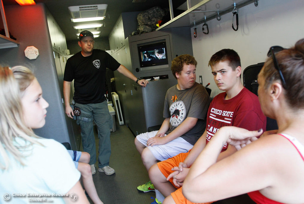 . Chico S.W.A.T team officer Alex Fliehr (center) answers questions inside the Regional Response vehicle as Kyle Carnagey and Dana Wheat (left to right) look around during the annual National Night Out Tuesday August 1, 2017 in Chico, California. (Emily Bertolino -- Enterprise- Record)