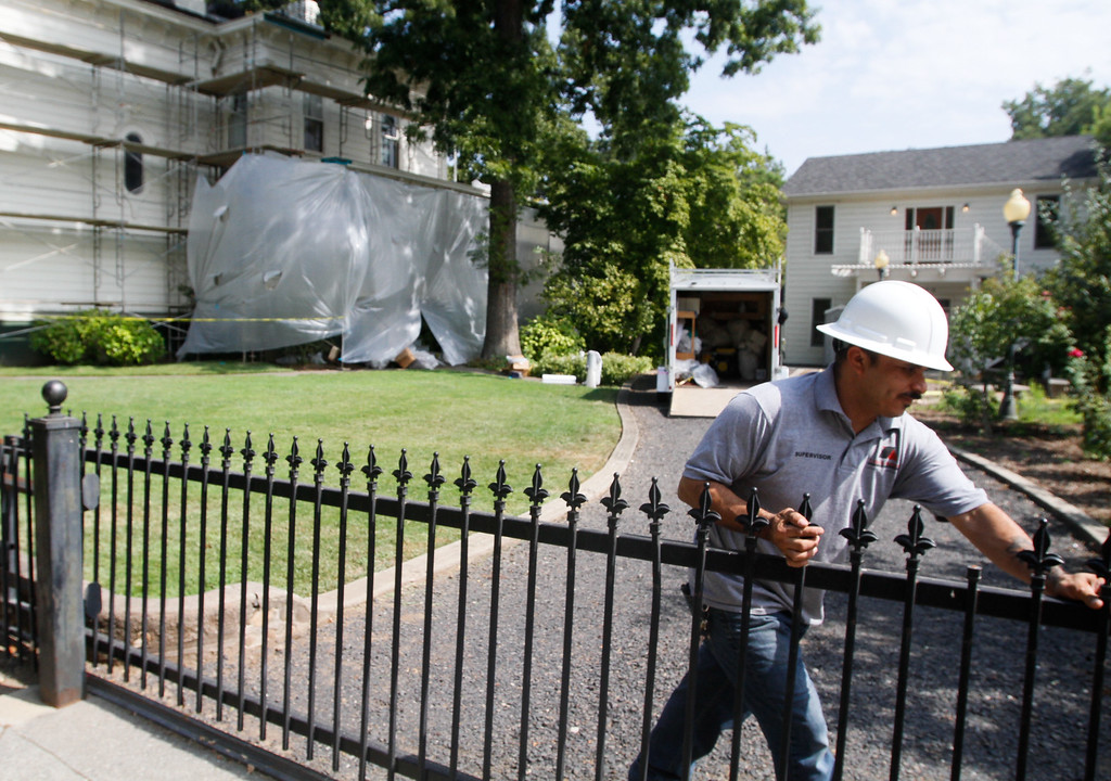 . Amado Zavala closes the gate as his crew works to scrape away old paint in preparation for a new coat on the Stansbury Home in a manner that will preserve it\'s historic significance September 6, 2017 in Chico, California. (Emily Bertolino -- Enterprise-Record)