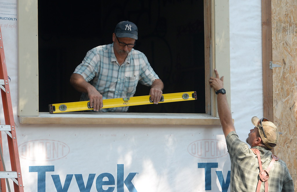 . Carpenters Chris Gauer and Donny Harp left to right install a window on the old Gothic house in it\'s new location in Chico, Calif. Tues. Sept. 5, 2017. (Bill Husa -- Enterprise-Record)
