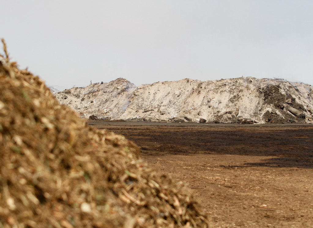 . A smouldering green waste pile next to green waste that was recently processed through a wood chipper, left, Wednesday September 6, 2017 at Old Durham Wood in Durham, California. (Emily Bertolino -- Enterprise-Record)