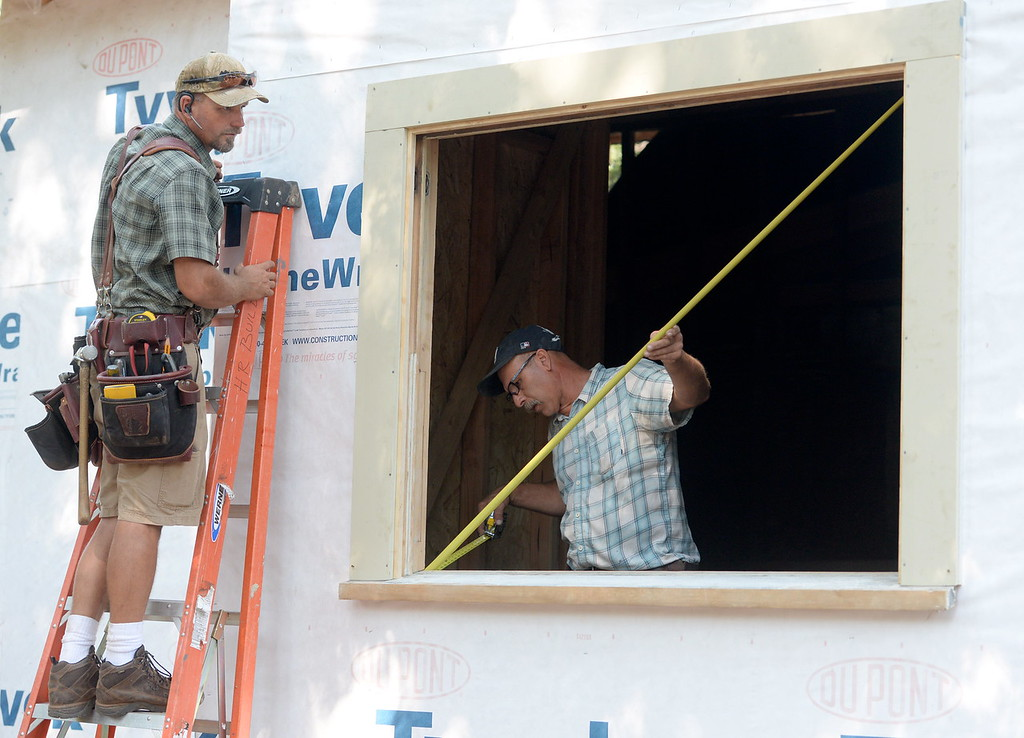 . Carpenters Donny Harp and Chris Gauer left to right install a window on the old Gothic house in it\'s new location in Chico, Calif. Tues. Sept. 5, 2017. (Bill Husa -- Enterprise-Record)