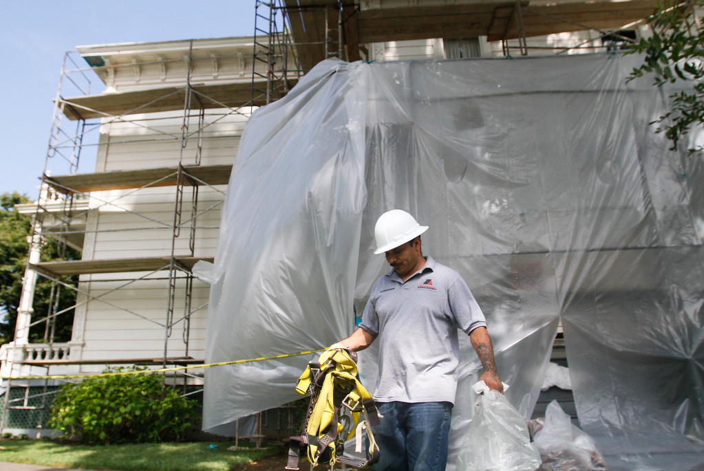 . Amado Zavala puts away harnesses as his crew worked to scrape away old paint in preparation for a new coat on the Stansbury Home September 6, 2017 in Chico, California. (Emily Bertolino -- Enterprise-Record)