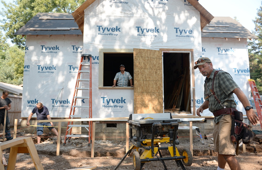 . Donny Harp at right rips a board on a table saw as they work on the old Gothic house in it\'s new location in Chico, Calif. Tues. Sept. 5, 2017. (Bill Husa -- Enterprise-Record)