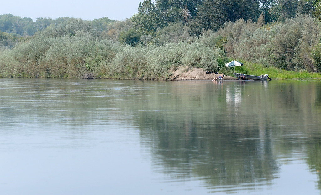 . A single boater is seen relaxing along the Sacramento River near the Pine Creek on a calm Labor Day Holiday on the river Monday, Sept. 4, 2017. (Bill Husa -- Enterprise-Record)