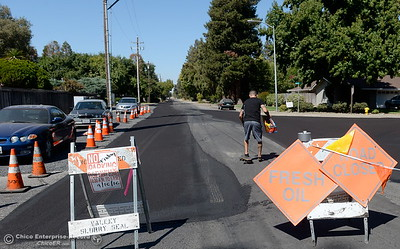 A skateboarder heads down a section of road not yet oiled on Morseman Ave. Friday as signs posted along Morseman Ave. warn residents of road closures for slurry seal work in the neighborhood Friday Sept. 16, 2016. The asphalt maintenance project is scheduled to be completed by Oct. 14th. (Bill Husa -- Enterprise-Record)