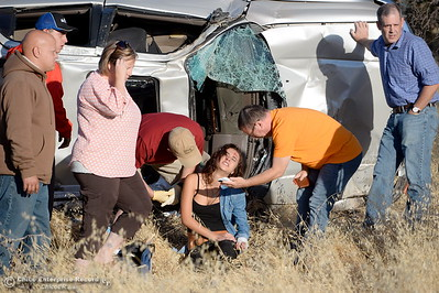 Witnesses and passersby stop to help following a single vehicle rollover accident below Lookout Point Thursday Sept. 15, 2016. A single female occupant sits on the ground beside the vehicle and appeared to be okay at the scene.(Bill Husa -- Enterprise-Record)