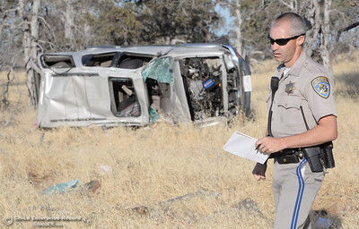 CHP Officer J. Cramblet investigates the scene following a single vehicle rollover accident below Lookout Point Thursday Sept. 15, 2016. A single female occupant sits on the ground beside the vehicle and appeared to be okay at the scene.(Bill Husa -- Enterprise-Record)