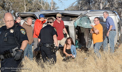 Witnesses and passersby stop to help as Paradise Police Officers arrive on scene following a single vehicle rollover accident below Lookout Point Thursday Sept. 15, 2016. A single female occupant sits on the ground beside the vehicle and appeared to be okay at the scene.(Bill Husa -- Enterprise-Record)