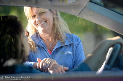 Program Assistant Margie Rackley smiles as she speaks to people in cars as a line forms along Springfield Drive during the annual Enloe drive through flu clinic held at the Calvary Chapel parking lot in Chico, Calif. Thurs. Sept. 22, 2016.  (Bill Husa -- Enterprise-Record)