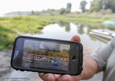 Deputy Sheriff Jay Waananen with the Marine Unit holds up a picture of what the annual Labor Day float use to look like with the now calm Sacramento River in the background Saturday September 2, 2017 in Chico, California. (Emily Bertolino -- Enterprise-Record)