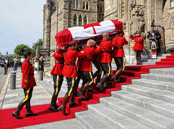Members of the Royal Canadian Mounted Police carry the coffin of Jack Layton, Canada's leader of the Opposition, into the Center Block of Parliament Hill in Ottawa, August 24, 2011. Photo by Patrick Doyle.