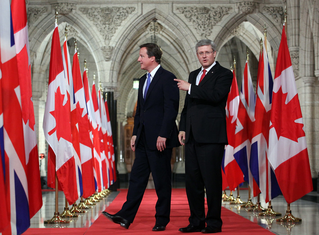 Britain's Prime Minister David Cameron and Prime Minister Stephen Harper walk down the Hall of Honour on Parliament Hill in Ottawa, Sep. 22, 2011.