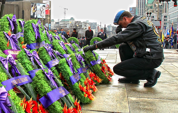 A veteran kneels after laying a wreath at the National War Memorial during Remembrance Day ceremonies in Ottawa, November 11, 2012. Photo by Patrick Doyle