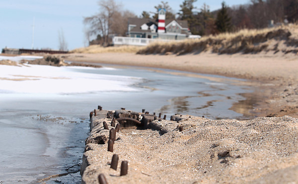 Record-Eagle/Nathan Payne<br /> A long piece of the center section of a shipwrecked boat extends into the water along the Lake Michigan shoreline near the Homestead Resort. The wooden structure was unearthed by violent winter storms that eroded the sandy beach that once covered the wood.