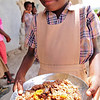 Photo courtesy of Jared Kohler<br /> A student at the Taifer school happily receives her mid-day meal. Students at the Taifer school walk up to four hours to attend classes and mid-day meals are important to provide the strength they need to complete their rigorous days of walking and studying.