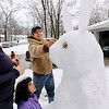 """Record-Eagle/Keith King<br /> Vicente Serrano, his wife, Anna, daughter Ava, bottom, 6, and son, Tavo, in back, 2, all of Traverse City, make a snow rabbit Wednesday, April 20, 2011 in their yard. The snow sculpture was started once the driveway was shoveled off. """"It's my birthday, I'm six,"""" Ava said, who had a snow day. Potatoes were cut in half and used for the rabbit eyes while a strawberry was used for the nose."""