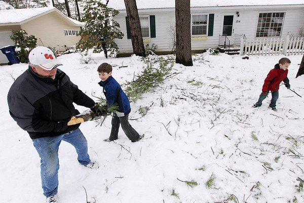 Record-Eagle/Keith King<br /> Alan Martin, left, of Ohio, removes fallen tree limbs Wednesday, April 20, 2011 with the help of his grandsons, Isaiah Stottmann, middle, 8, of and Jeremy Stottmann, right, 6, of Traverse City.