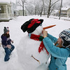 Record-Eagle/Keith King<br /> Tess Crowley, right, 10, of Traverse City, and her sister, Natalie Crowley, 7, take advantage of the snow as they make a snowman Saturday, March 3, 2012 in Traverse City.