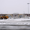 Record-Eagle/Keith King<br /> A front-end loader with a plow attachment clears snow from the parking lot in front of Kohl's, which was closed at the time the photograph was taken, Saturday, March 3, 2012 in Traverse City.