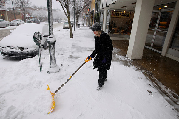 Record-Eagle/Keith King<br /> Gus Walworth, manager at Golden Shoes, shovels snow from the sidewalk Tuesday, January 17, 2012 in downtown Traverse City.
